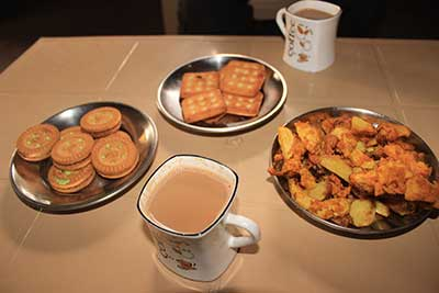 Indian Masala Chai Tea served with Biscuits and aaloo pakauda